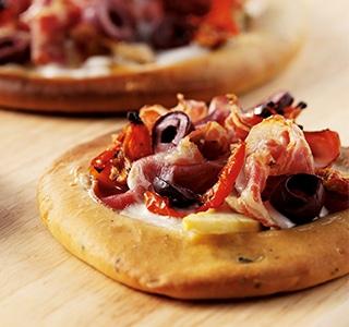 Pizza mit Ziegenkäse, Parmaschinken und frischen Oliven