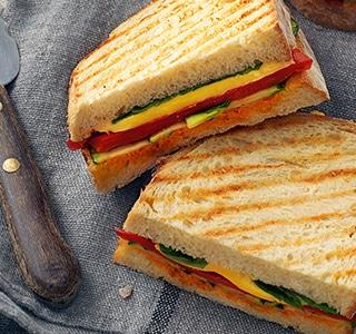 Toast mit Cheddar, gegrilltem Gemüse und rotem Pesto