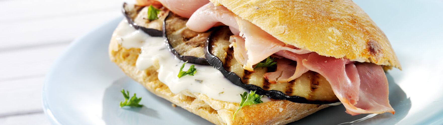 Ciabatta roll with ham, roasted aubergine and fresh herbs