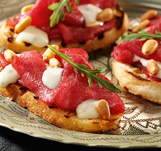 Crostini with carpaccio, rocket and pine nuts