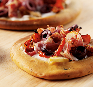 Pizza with goat's cheese, Parma ham and fresh olives