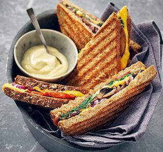 Tosta-mista com queijo cheddar, salame, cogumelos Portobello, espinafres e maionese com trufa