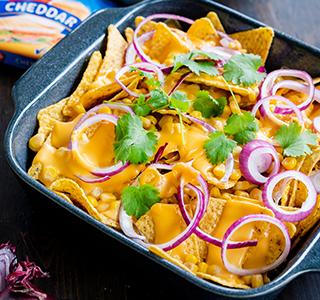 Nachos com queijo, cebola roxa, milho, guacamole e coentros