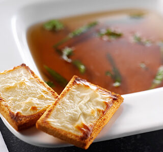 Beef consommé with haricot verts and toast with ERU Spreadable Goat Cheese