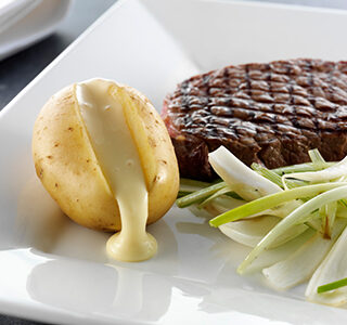 Grilled prime rib served with potatoes filled with ERU Spreadable Gouda, and braised fennel