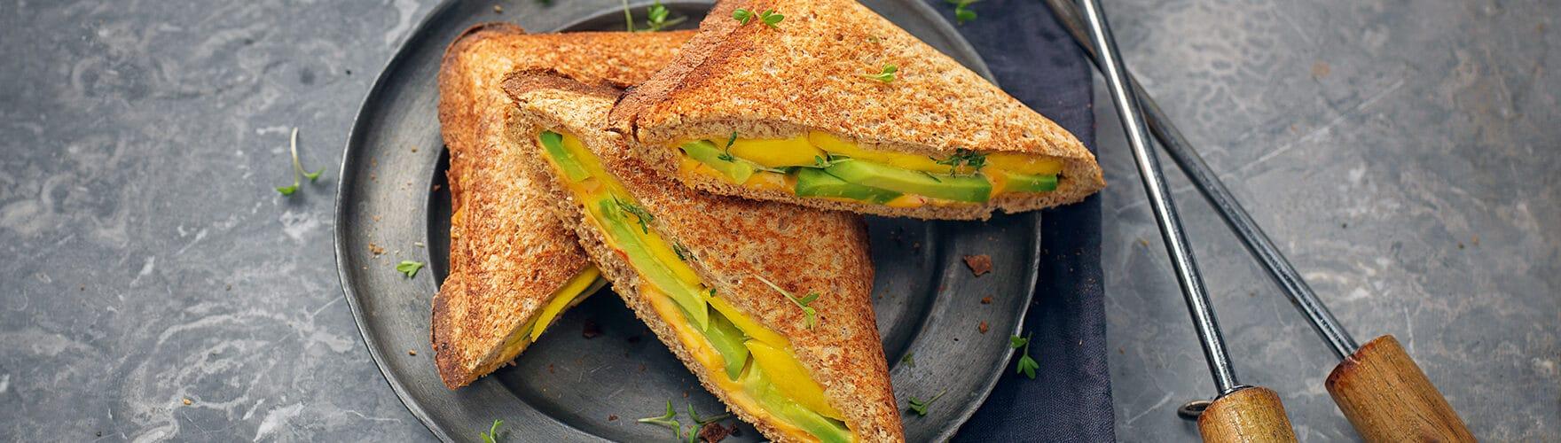 Tosti met cheddar, avocado, mango, tuinkers en sambal