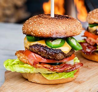 Cheeseburger met cheddar, bacon, jalapeño pepers, tomaat en sla