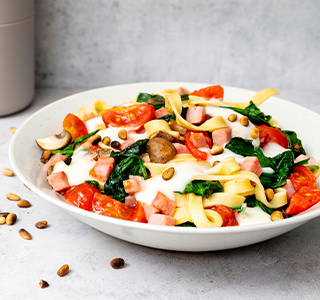Verse tagliatelle met hamblokjes, spinazie, champignons, trostomaten en pijnboompitten