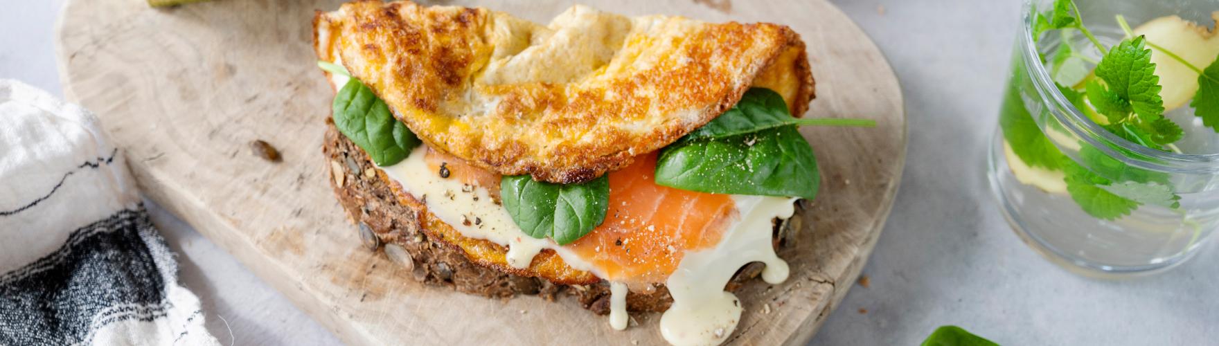 Boeren boterham belegd met een omelet, biologische kaas, zalm en babyspinazie