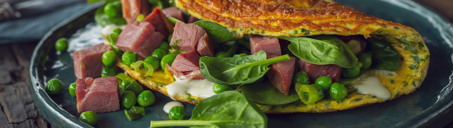 Dubbelgeklapte omelet met tuinkruiden, voorjaarsgroenten, lamsham en blauwe kaas