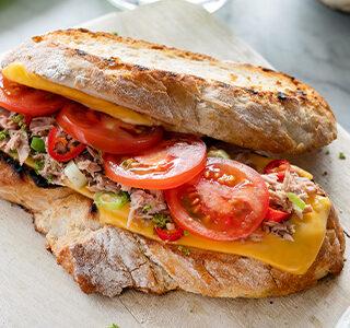 Tuna melt tosti met plakjes cheddar, lente-ui, rode peper, tomaat en limoen