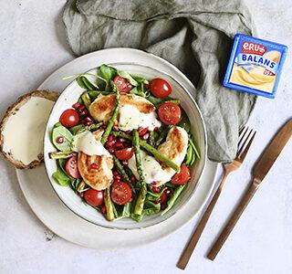 Maaltijdsalade met verschillende groenten, krokante kip, granaatappelpitjes en een dressing van belegen magere kaas met limoenrasp