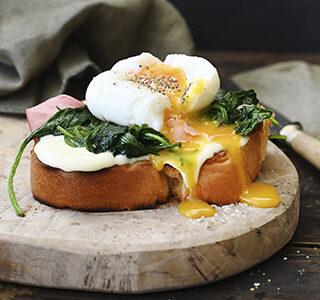 Brioche brood met ham, spinazie, roomzachte smeerkaas en een zachtgekookt eitje