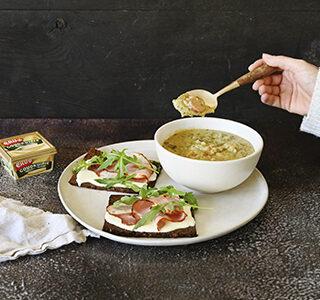 Erwtensoep en roggebrood belegd met roomzachte smeerkaas, katenspek en rucola