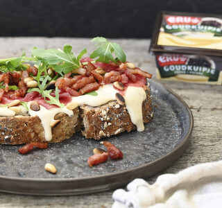 Landbrood met carpaccio, spekjes, rucola, pijnboompitten en kaas