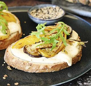 Sandwich met gegrilde groenten, rucola, roomzachte smeerkaas en sesamzaadjes
